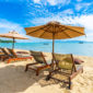 Beautiful tropical beach sea and ocean with coconut palm tree  and umbrella and chair on blue sky and white cloud for holiday vacation travel